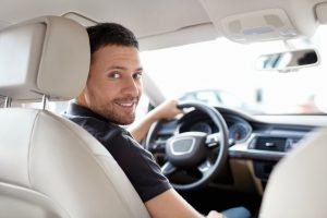 Man smiling in the driver's seat. Sherman Oaks Title Loans