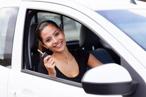 Girl with key in white car. Hayward Title Loans