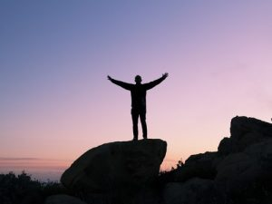 Man with open arms standing on rock