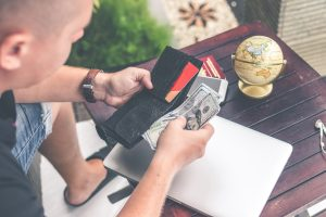 Man with money in wallet. Title Loans Express can help you get the loan you need
